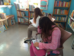 Two young patrons reading at the Lampedusa library. Photo courtesy of Mariella Bertelli.
